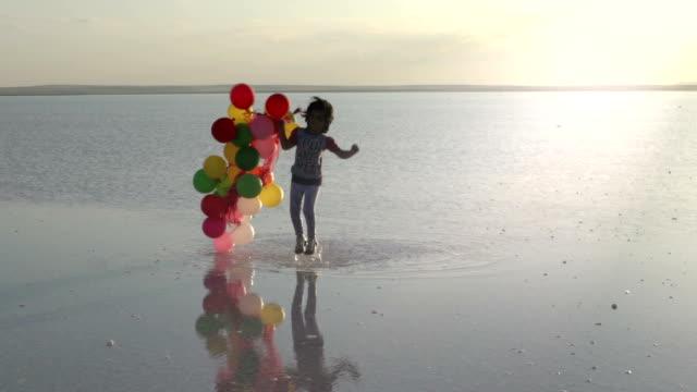 vidéos et rushes de petites filles marchant sur l'eau avec des ballons de couleur slowmotion - ballon de baudruche