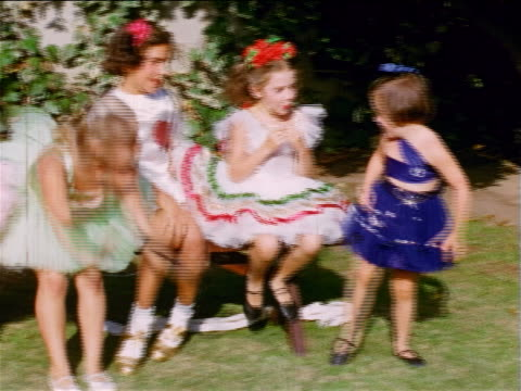 1953/54 home movies pan little girls with ballerina costumes sitting on bench + bending - ballet dancer stock videos & royalty-free footage