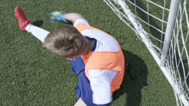 little goalkeeper stretching on stadium field - soccer glove stock videos and b-roll footage
