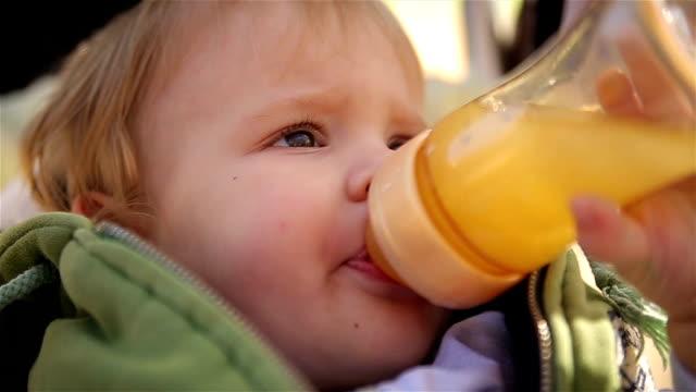 A little handsome boy drinks juice