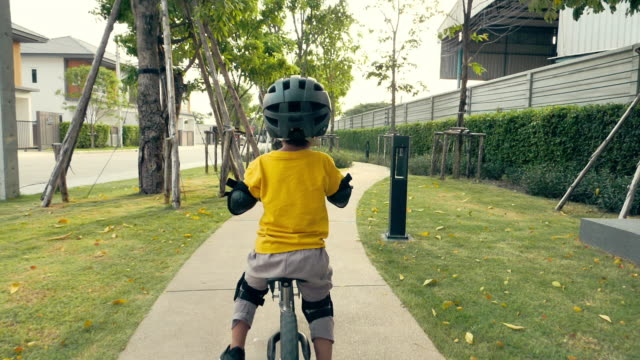 little happy boy riding bike on bike lane in the park - baby boys stock videos and b-roll footage
