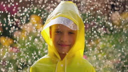 Little happy cute boy child wearing yellow raincoat and enjoying having fun rainfall. Kid looking at camera, playing with rain sunlight. Happy family summer autumn fall childhood concept, 120 slow-mo