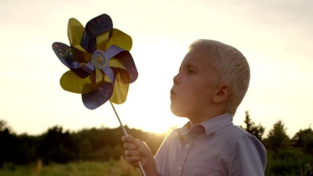 piccolo ragazza felice con pinwheel sequenza - girandola video stock e b–roll