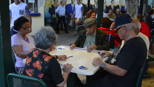 vídeos de stock, filmes e b-roll de little havana in miami florida playing dominoes in the senior recreational center having fun - corte transversal