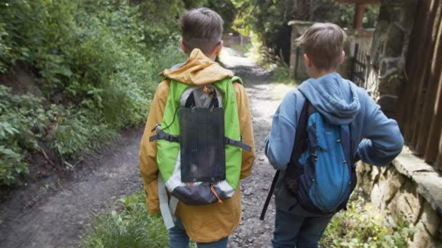vídeos de stock e filmes b-roll de little hikers using solar cells on backpack - cena não urbana