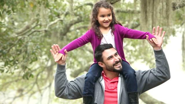 Little Hispanic girl sitting on father's shoulders