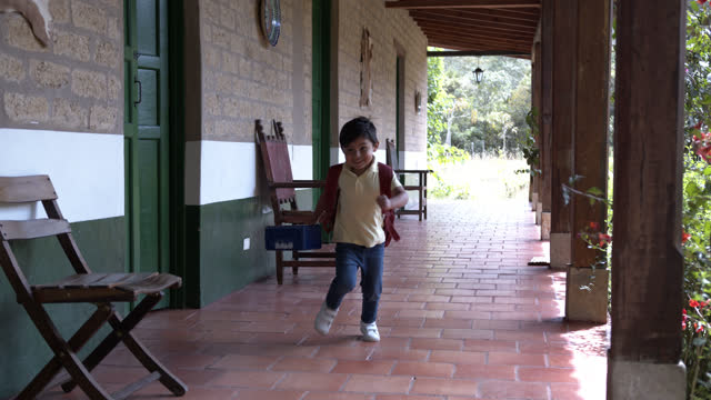 little latin american boy looking very excited to go back to school and running towards the camera carrying his backpack and holding his lunchbox - colombia stock videos & royalty-free footage