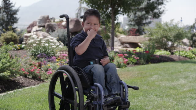 little latino boy sitting in a wheelchair in front of a rock and flower garden - wheelchair stock videos and b-roll footage