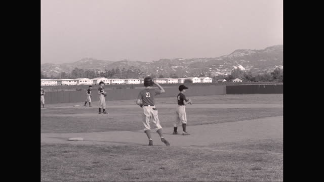 ws pan little league baseball game, batter runs to first base / united states - little league stock videos and b-roll footage