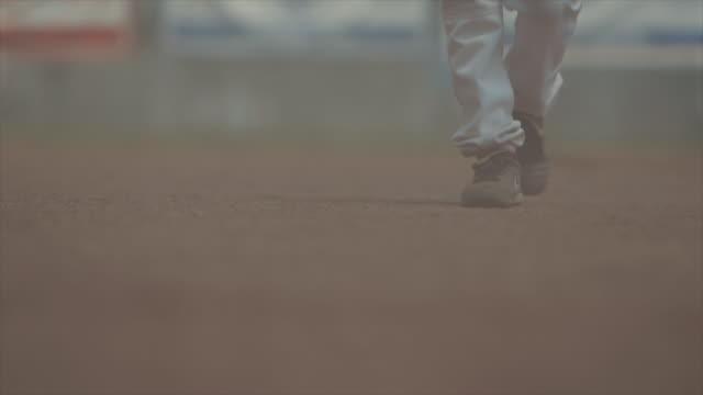 Little league baseball player walking on dirt field