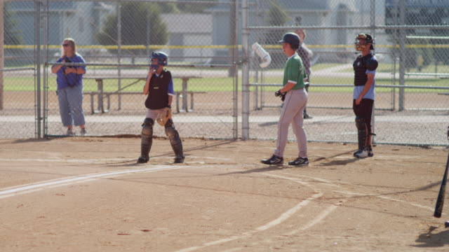 Little league baseball practice in a small town. Shot features a batter at the plate and a catcher. Batter swings - strike!