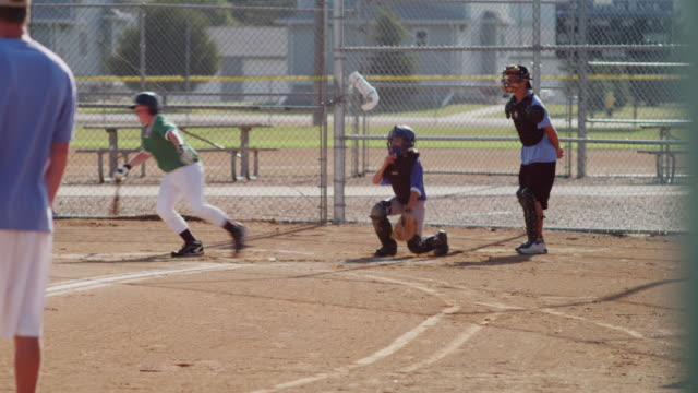 vídeos y material grabado en eventos de stock de little league baseball practice in a small town. shot features a left-handed batter at the plate and a catcher. this pitch is thrown - batter connects! - batear
