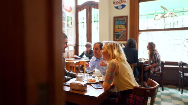 vidéos et rushes de petit homme passant le temps de qualité avec des amis dans la cafétéria - restaurant