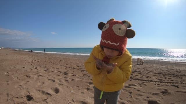 vidéos et rushes de peu de jouer à la plage en hiver jour ensoleillé. - casquette