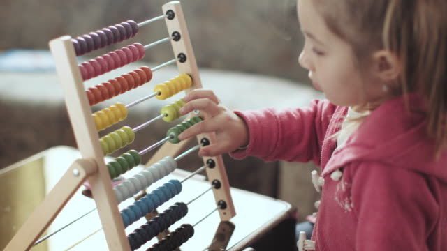 little preschooler with abacus learning cute little girl, playing with an abacus at home, sunny living room. stock video... - genius stock videos & royalty-free footage