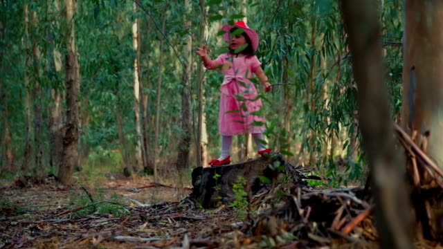 Little princess in the forest standing on stump