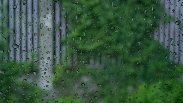 little rain drops running down the window surface at home or car with house fence wall background - wet stock videos & royalty-free footage