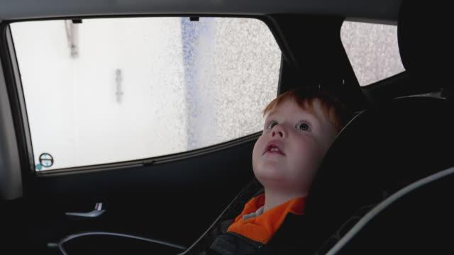 little red head småbarn beeing imponerad inuti en biltvätt - biltvätt bildbanksvideor och videomaterial från bakom kulisserna