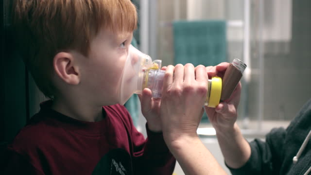 little redhead boy getting breathing treatment from mother - allergy stock videos & royalty-free footage