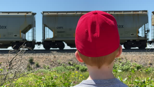 little redhead boy watches a commercial train pass by a railroad track in redcliff, canada on june 20, 2020. - daydreaming stock videos & royalty-free footage