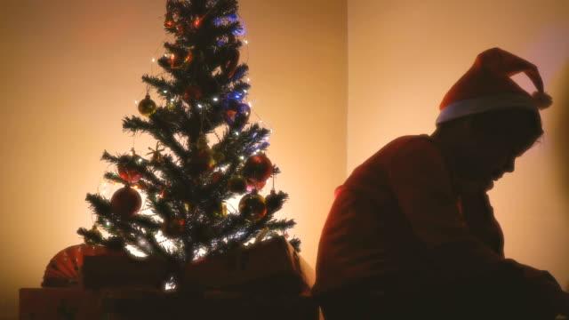 vídeos de stock, filmes e b-roll de menino triste pequeno que senta-se perto da árvore de natal - tristeza