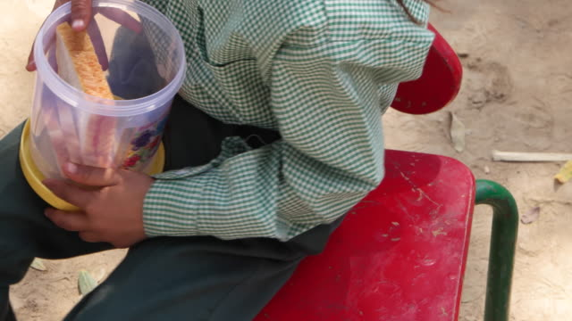 a little school girl having lunch during a break from her class, pan down to her tiffin - lunch stock videos & royalty-free footage