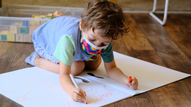 little schoolboy drawing lying on the floor wearing a protective face mask - child care stock videos & royalty-free footage