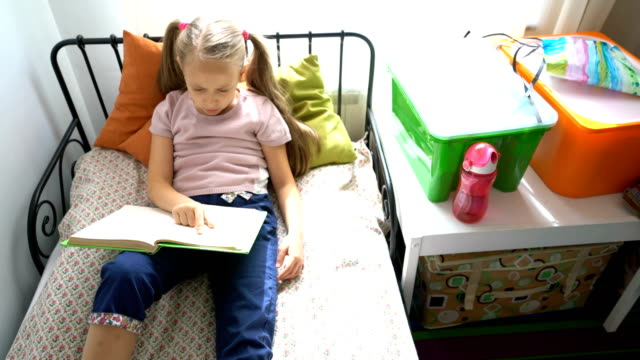 little schoolgirl reading her book slowly - schoolgirl stock videos and b-roll footage