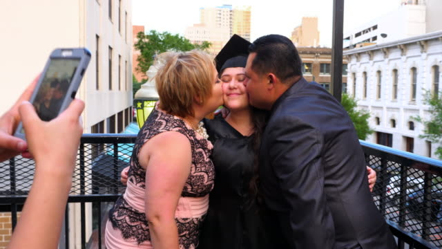 ms ts little sister taking photo with smartphone of parents kissing graduating daughter during family celebration - 18 19 years stock videos & royalty-free footage