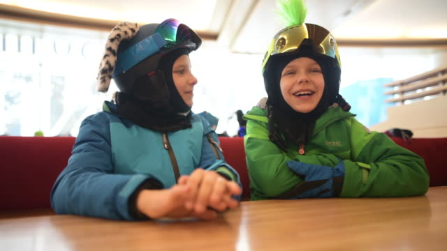 little skiers waiting for lunch in alpine ski restaurant - sports helmet stock videos & royalty-free footage