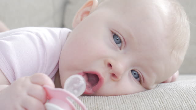 little small girl playing with pacifier while lying on sofa - pacifier stock videos and b-roll footage