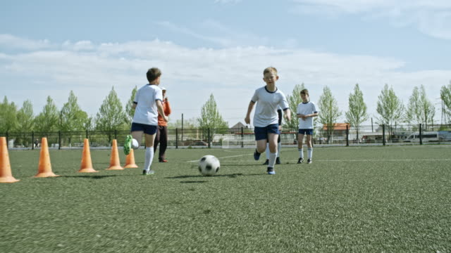 Little soccer athletes practicing passing and receiving ball