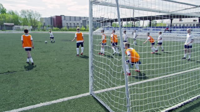 Little soccer player performing kick and losing during training match