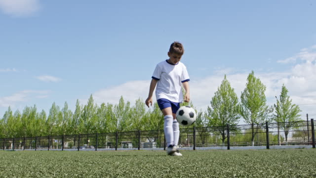 little soccer player practicing juggling the ball on stadium - fähigkeit stock-videos und b-roll-filmmaterial