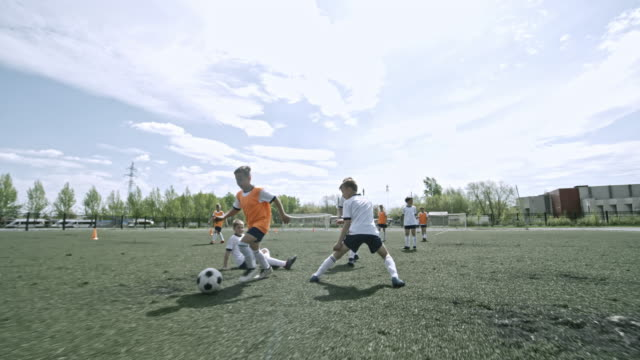 Little soccer player scoring a goal during training game