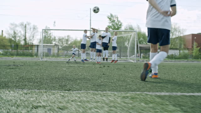 little soccer player scoring from free kick while training on playing field - 男の子点の映像素材/bロール
