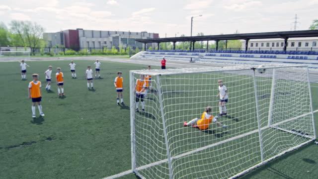 Little soccer player shooting ball into net during match