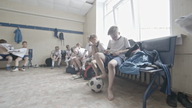 little soccer players changing clothes in locker room - socke stock-videos und b-roll-filmmaterial