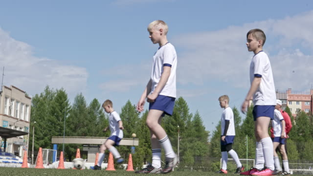 stockvideo's en b-roll-footage met little soccer players training shooting the ball - oefenen