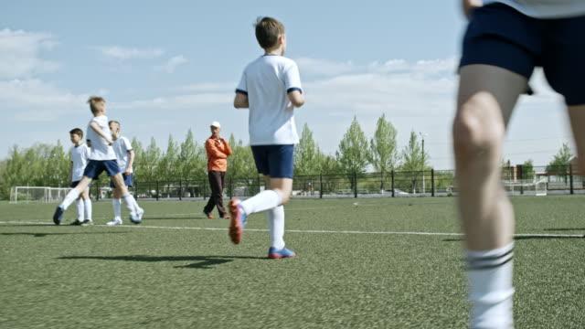 little soccer professionals training dribbling and passing - 渡す点の映像素材/bロール