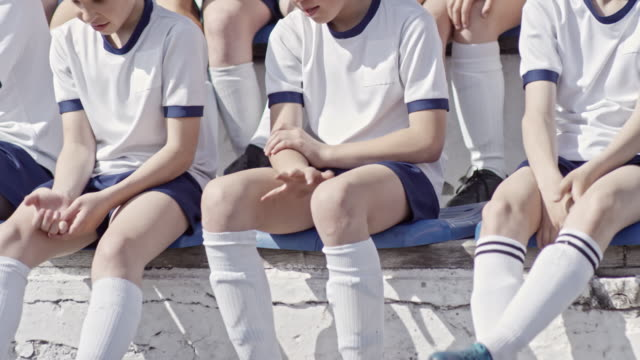 Little soccer team sitting on bleachers, chatting and playing hand game