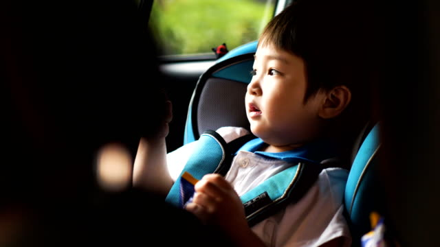 little thai baby boy is sitting on safety car seat and eating snack with her mother before go school-on the car - on the move stock videos & royalty-free footage