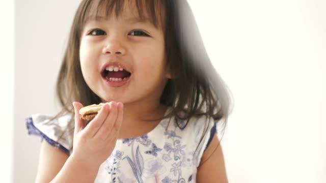 タイの女の子は彼女の部屋にいくつかのクッキーを食べることを楽しむ - おやつ点の映像素材/bロール