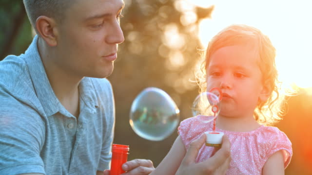 slo mo little toddler girl blowing bubbles with father's help in the setting sun and smiling - mid adult men stock videos & royalty-free footage