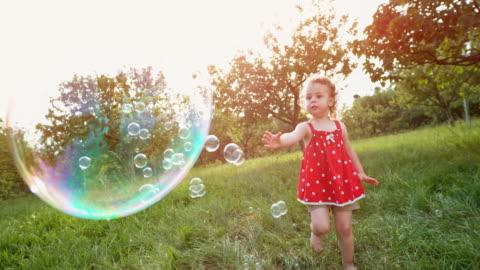 vidéos et rushes de slo mo bambin fillette en tunique rouge, attraper les bulles de savon dans le verger - vie simple