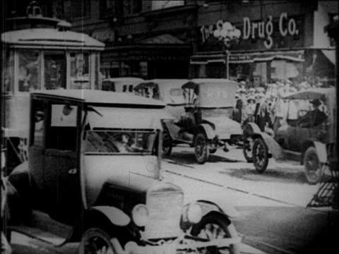 b/w 1923 little tramp crossing street against heavy traffic + trolleys / los angeles / feature film - tram stock-videos und b-roll-filmmaterial