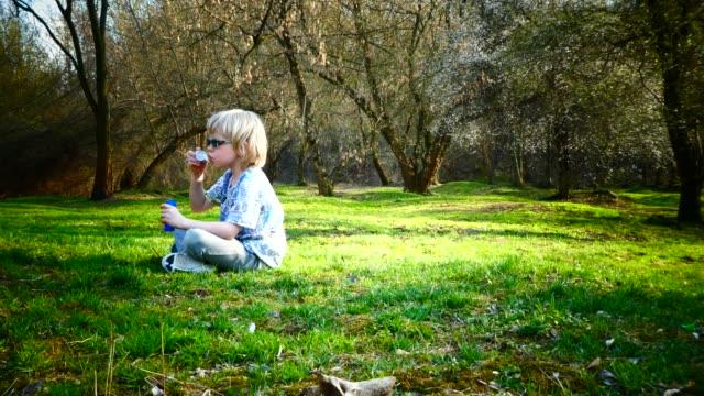 vídeos de stock, filmes e b-roll de menino jovem brincando com bolhas de sabão durante o dia de sol. - sentando