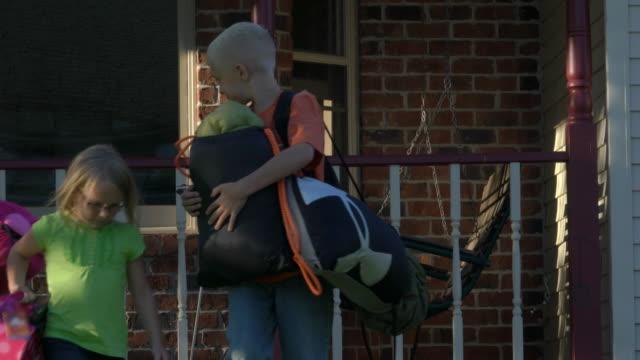 Littlel girl puts suitcase in mini camper, CU