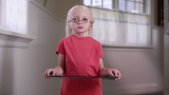 Litttle blond girl with Cochlear Implant standing in a hall way holding her baby picture