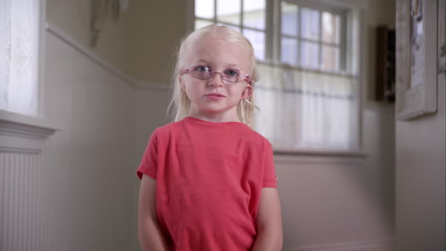 Litttle blond girl with Cochlear Implant standing in a hall way
